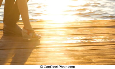 Couple walking on the pier at sunset