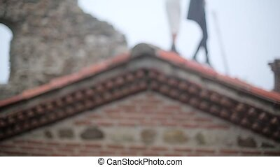Couple walking on the roof of old building