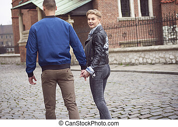 Couple walking on the street and holding hands