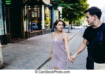 couple walking on the street holding hands