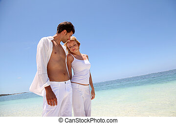 Couple walking on white sandy beach