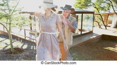 Couple walking on wooden boardwalk 4k - Happy couple walking...