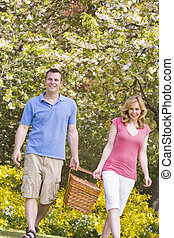 Couple walking outdoors with picnic basket smiling