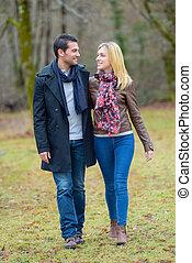 Couple walking through a park