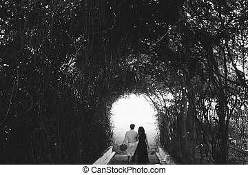 couple walking through the tunnel of trees