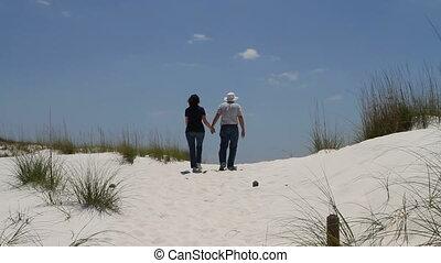 Couple Walking Up Dune