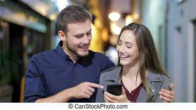 Couple walking using a smart phone in the night