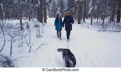 couple walking with a dog Husky
