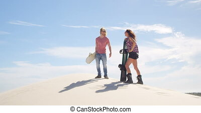 Couple walking with sand boards in the desert 4k - Couple...