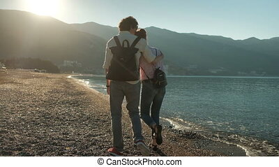 Couple walks along the beach in evening on a background of mountains.