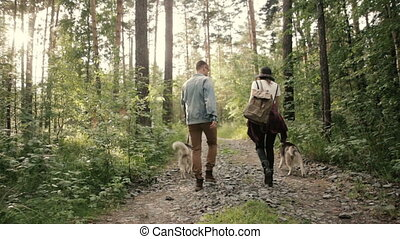 Couple walks in woods with dogs and looks around