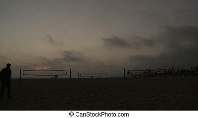 Couple Walks on Beach at Sunset
