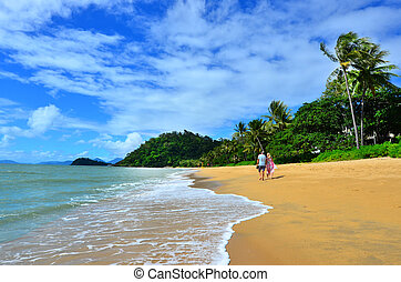 Couple walks on Trinity beach near Cairns Queensland Australia