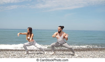 Couple warming out outdoors, doing squats together