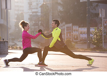 couple warming up before jogging