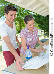 Couple washing dishes on campsite