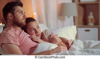 couple watching horror on tv in bed at night