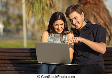 Couple watching media in a laptop sitting on a bench