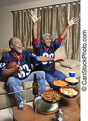 Couple watching sports. - Middle-aged African-American...