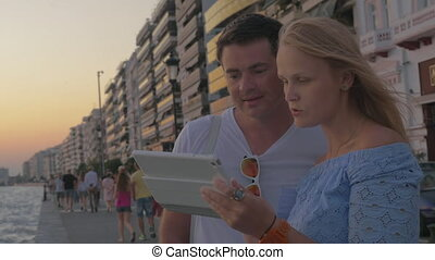 Couple watching tablet at the beach