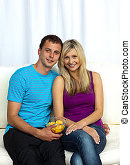 Couple watching television and eating crisps