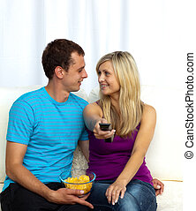 Couple watching television on sofa and eating crisps