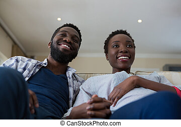 Couple watching television together in living room