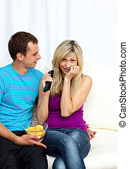 Couple watching television together on sofa