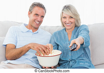 Couple watching tv and eating popcorn on the couch