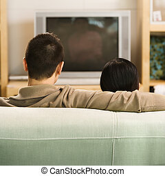 Couple watching TV. - Asian couple sitting on couch watching...