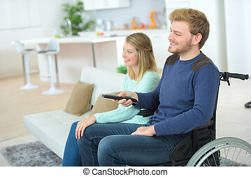 couple watching tv at home man sitting on wheelchair