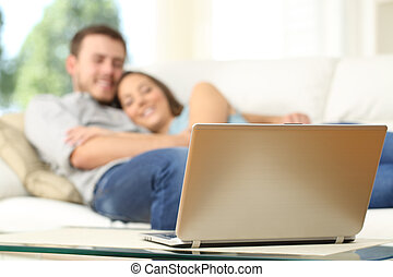 Couple watching tv in a laptop lying on a couch at home