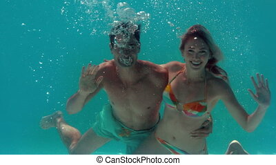 Couple waving at camera underwater