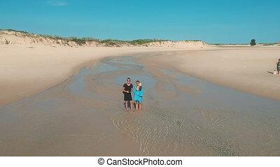 Couple Waving from Sandy Beach Aerial Panorama