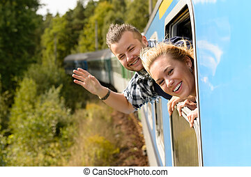Couple waving with heads out train window enthusiastic...