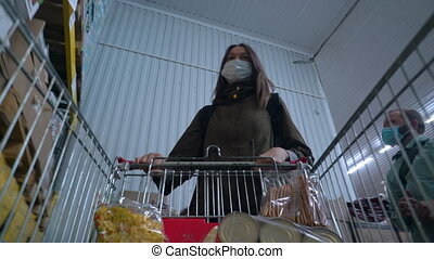 Couple wearing a medical mask walks through an empty supermarket or grocery store and buys food. Quarantine and self-isolation, covid-19 epidemic, coronavirus pandemic. Protection against coronavirus.