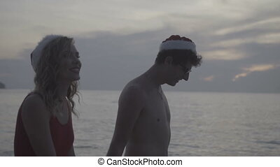 Couple wearing santa hat at the beach
