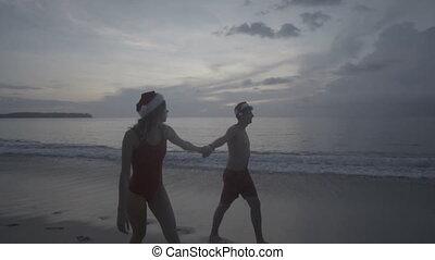 Couple wearing santa hat at the beach