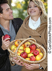 Couple with a basket of apples