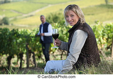 Couple with a glass of wine in the vineyard