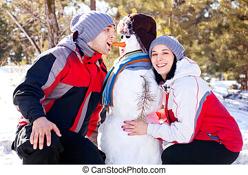 couple with a snowman