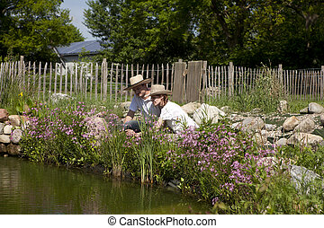 couple with a straw hat on the garden pond, pärchen mit...