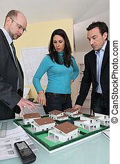Couple with an architect looking at a housing model
