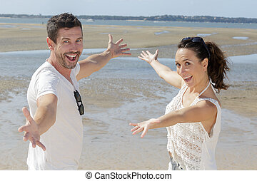 couple with arms wide open enjoying the ocean