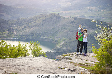 Couple with baby boy standing on cliff and kissing