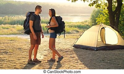 Couple with backpack on nature - Young man and woman hiking...
