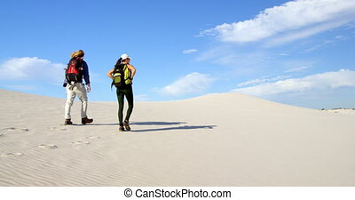 Couple with backpack walking in the desert 4k