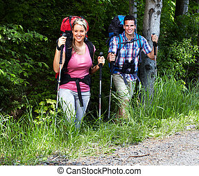 Couple with backpacks and trekking poles. Hiking people
