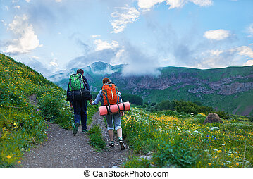 Couple with backpacks going to hike, climb mountain along...