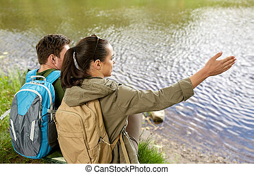 couple with backpacks sitting on river bank